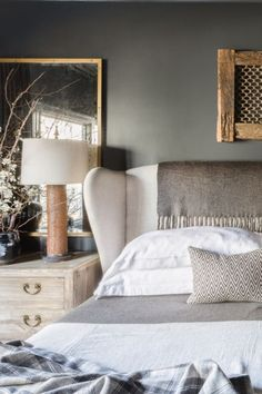 A cream colored headboard sits against a dark gray wall in a modern country home in east Memphis.