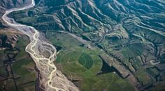 Aerial view of glacial fed braided river, centre pivot irrigation on floodplains and sheep grazed hill country. The bold patterns of fossil fue powered landuses overlaying the crisp land forms of geologically young New Zealand South Island landscapes