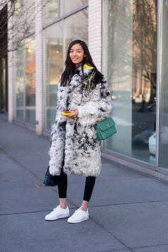 Winter Street Style Outfit: black and white fur coat styled with leggings and clean white sneakers—casual, but cool.