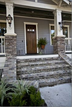 Another great way to incorporate stone to the exterior of your home. Stone steps, white trim, gray siding and a wood front door