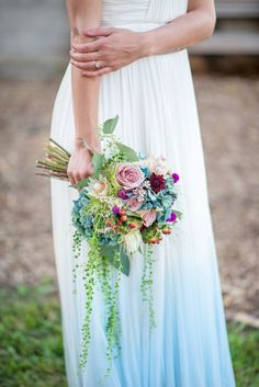 Petal Pusher used roses, hydrangeas, dahlias, 'Blushing Bride' proteas, scabiosas, berries, and string of pearls to create this beautifully eclectic bouquet. The bespoke dip-dyed dress was designed by Minkmaids. | Photo by Kasey and Ben Photography