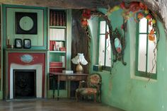 I adore everything about this room ~ the turquise walls ~ autumn leaves growing in from outside and the glorious furniture and huge amount of well worn books!!!! from NINETTE & CO
