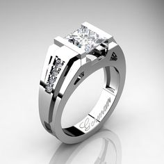 Luxurious, elegant and classy, Mens Modern 14K White Gold 2.0 Carat Princess Russian CZ Diamond Ring G1094P-14KWGDRCZ by Gorman Designs, evokes character and style. This modern mens ring showcases a 2.0 carat princess cut Russian CZ center gemstone accented with 8 x round 0.015 to 0.020 carat top quality VS-SI G-H white diamonds set in 14K white gold. All sizes are available up to finger size 12 at no additional charge. Includes:  * 1 x approx 8.0 grams TW of cast solid 14K white gold ring…