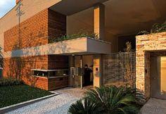 O detalhe da fachada mostra a combinação entre pedras, madeira e concreto. A guarita tem visor com beirais em balanço