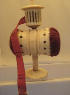 """1825 - stand alone pin cussion & tape measure combo in antique bone - Victorian :  bone needleworker combination piece 4"""" high - the piece is topped by a tape measure cage containing its original 2 1/4 foot-long silk tape. Beneath is a 1 1/4"""" diameter """"barrel"""" containing the twin pin cushions."""