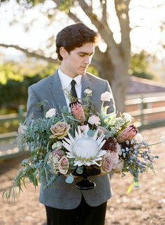 White king protea, roses, in a smoke glass compote arrangement. Diana Marie Photography