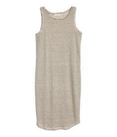 Lichtbeige/gestreept. Een mouwloze tricot jurk van linnen. De jurk is licht afgerond aan de onderkant.