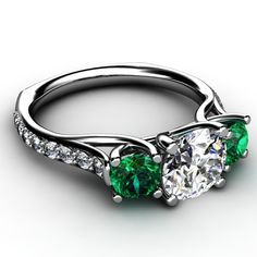 Platinum three stone diamond and emerald trellis designed engagement ring with small diamond accents down ring shank