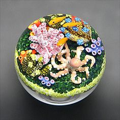 Cathy Richardson paperweight. An octopus can camouflage itself by changing its color and pattern to match the background. Here we seen one resting between corals and sea grass keeping a watchful eye on the surroundings.