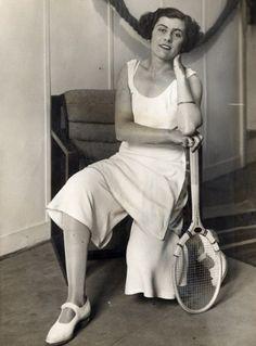 Senorita Lili De Alvarez, later Comtesse De Gaillard De La Valdene, wears a skirt/culotte hybrid, gold arm bangle and white Mary-Janes in 1931. .