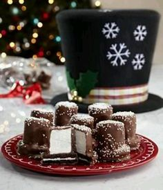 """Frost's Hat cookies:  Oreos with a marshmallow. Then dip in melted chocolate.  Sprinkle with edible white """"snow"""" / glitter while chocolate is still sticky.  You may need to attach the oreo & marshmallow together using a tad bit of frosting so they stay together while you are dipping in chocolate. Lay on tray covered with wax paper to until hardened.  Transfer to serving dish.  Perhaps sprinkle with some powdered sugar for more """"effect."""""""