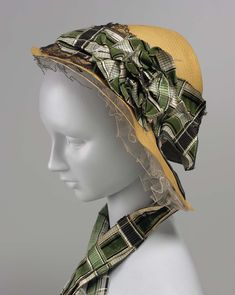 """Bonnet, American, 1850s.   Museum of Fine Arts, Boston. 43.1583. """"Woman's bonnet, leghorn trimmed with plaid ribbon and black lace. Straw, trimmed with silk plain weave (taffeta) and silk voided-velvet ribbon; machine lace."""""""