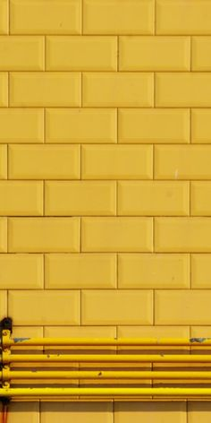 Yellow // Tiled wall + steel pipes all in yellow.