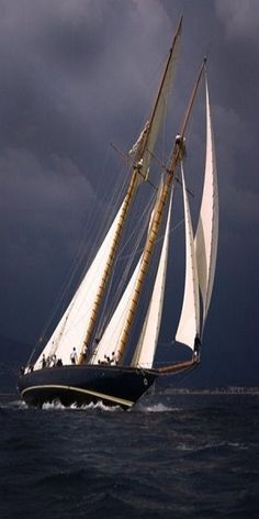 Schooner. Stunning photo of sun-bathed sails with a dark, brooding sky in the background.