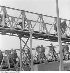 View of an inclined metal walkway, with people pushing bicycles seen through the wire sides. Place Kent From a group of negatives labelled 'Headcorn/ Sep April Date Sep 1963 - Apr 1964