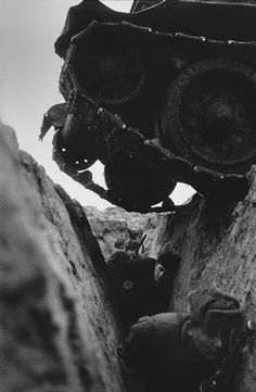 Russian soldiers duck as tanks pass over them, WWII.