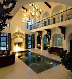 Black and white Dream Home. A indoor pool next to a fire place
