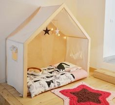 lit-maisonnette-toile-bois-matelas-mobile-bébé-étoiles-en-tissu-revêtement-sol-bois-tapis-tricot-en-forme-d-étoile-idée-chambre-montessori-simple