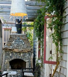 Awesome outdoor patio with driftwood fireplace and river rock mosaic surround