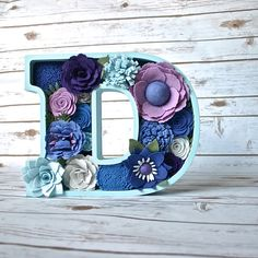 Hand cut birch wood letter filled with handmade felt flowers in lovely shades of blue.