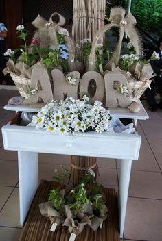 Mesinha mudas de flores para lembranças dos convidados decorada com letras forradas e cestas