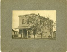 An exterior photograph taken in 1902 of John Knickrehm's store, located on West 4th Street and Pine Street in Grand Island, Nebraska.  The two story building has advertisements painted on the sides of building.  The gentleman sitting on the front stoop is identified as Henry Schipmann.