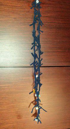 Calza di nylon coprente blu legata con perle di vario genere.