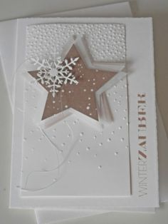 handmade winter card from Mia's blog .. white and taupe ... falling snow embossing folder ... pile of die cut stars placed akilter ... delicate die cut snowflake tops it off ... avant guard look ...