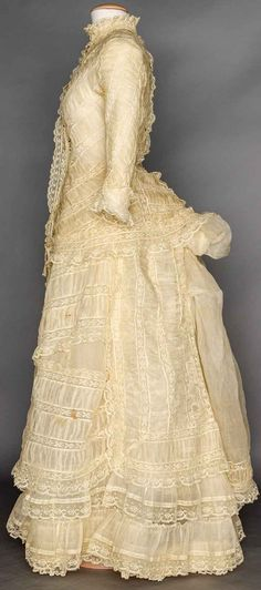 """2-piece, ruched organday bands alternate w/ Valenceinnes lace, tubular sleesves on cuirass bodice & narrow bell skirt, B 34""""-36"""", W 27"""", Skirt L 39""""-43"""", (brown stains, discolorations under arms, seam separations) very good."""