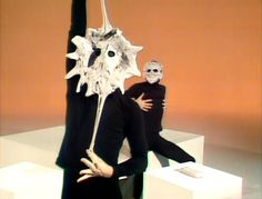 The Mummenschanz perform with masks made of clay. As the scene progresses, they add more and more clay, changing their appearance. The one character is jealous of the other's ability to make beautiful sculptures with his face. Soon, this devolves into a battle in which they eventually find themselves stuck to each other.