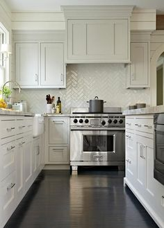 A white and gray transitional kitchen boasts dark stained oak wood floors and ivory shiplap walls.