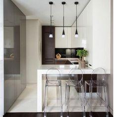 Laca branca, fendi e um madeirado escuro compõem essa cozinha americana que ficou um luxo. A bancada em super nano foi realçada pelos pendentes sobre a mesma. E essas banquetas em acrílico????? Ameiiiii