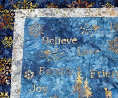 Blue Batik Wall Hanging or Table Topper with Winter Snowflakes, deer, pine trees and expressions from Mountain Quiltworks