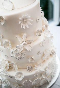 Modern, four-tier white wedding cake with fondant daisy flowers (Meredith Hanafi Photography)
