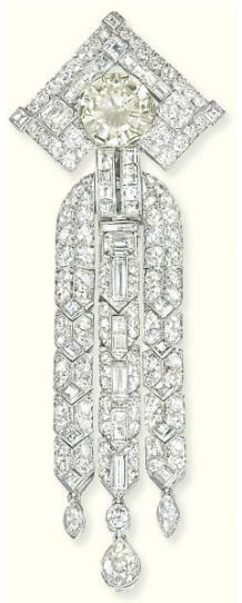 AN ART DECO DIAMOND PENDANT/BROOCH   The circular-cut diamond weighing 5.84 carats within a mitre-shaped surround with square-shaped diamond line and corner detail suspending a triple line tassel of vari-cut diamond links with marquise-and pear-shaped diamond drops, circa 1930, 10.4 cm long, with French assay marks for platinum