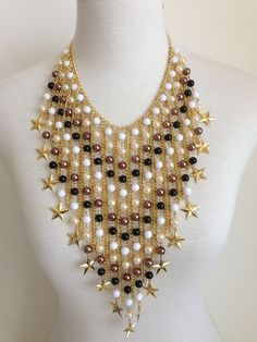 Maxi colar feito com pérolas, contas sintéticas, franjas douradas e estrelas douradas nas pontas. R$ 120,00
