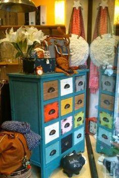 Mueble vintage azul con cajones de colores y tiradores retro, en el escaparate de VYP, Palma.