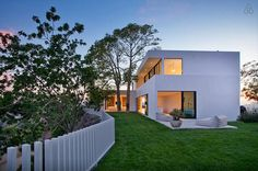 From a Distance  A sunset highlights the perfectly minimal facade and a modern take on a white picket fence.