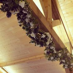Rose garlands archway with silver pine cones and ivy. Lovely for a winter wedding.