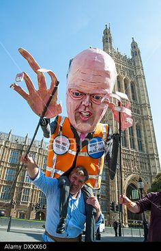 London, UK. 1st April 2014. Giant puppet of Chris Grayling, Secretary of State for Justice, is held up in front of the Houses of Parliament during protest against cuts to legal aid. © Pete Maclaine/Alamy Live News