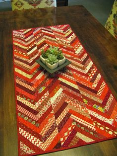 Herringbone Braid Table Runner made with Triangles On A Roll Sew and Fold Braid Paper. So easy to do! And a great way to use scraps. Patchwork Table Runner, Table Runner And Placemats, Quilted Table Runners, Fall Quilts, Scrappy Quilts, Mini Quilts, Quilting Tutorials, Quilting Projects, Braid Quilt
