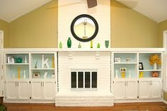Brick fireplace painted white, flanked by built-ins