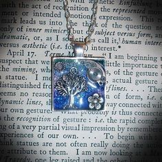 """The Spirit of the Universe Pendant - Silver plated square pendant with an engraved tree and vintage clock parts set in resin on a glittering blue and purple sky background. Size - 2.5cm x 2.5cm. Comes on a silver plated chain - 16.5"""" - 18"""" long, with a small engraved silver plated wing at the end of the extender chain. Gift wrapped. Price - £14.99 plus £2.99 p&p."""
