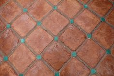 Terracotta floor with small turquoise tile at the corners