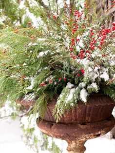 A no-fuss pairing of Port Orford cedar and winterberry holly stems provides a festive touch to a front entry.