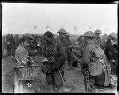 A Maori soldier (1st Canterbury Regiment) buying cakes from a local woman while halting in training exercise. Other soldiers and another female vendor nearby. Photograph taken 1917 by Henry Armytage Sanders.