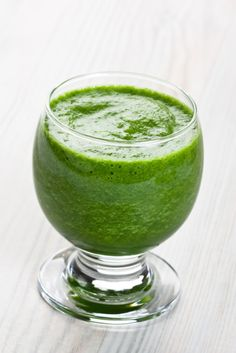 A clear glass filled with a creamy bright green smoothie.