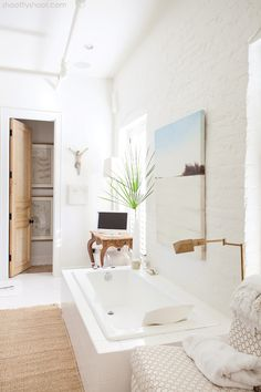 Atchison Home - bathrooms - country bathroom, art over bathtub, white brick wall, painted brick wall, drop in bathtub, table with cabriolet legs, cabriolet table, slipper chair, geometric slipper chair, floor lamp, antique brass floor lamp, jute rug,
