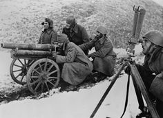 Greek soldiers fight the Italian Fascist invasion in the mountains of Albania in November 1940. In this photo, they prepare to fire a 65mm mountain gun. The artillery target officer is on the right calculating the trajectory.