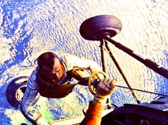 Here Mercury astronaut Alan Shepard pulled up by helicopter from capsule after landing in Atlantic, May 1961: